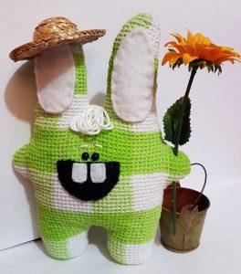 Ein grüner Stoffhase mit einer großen Blume, einem Eimer und einem Strohhut.
